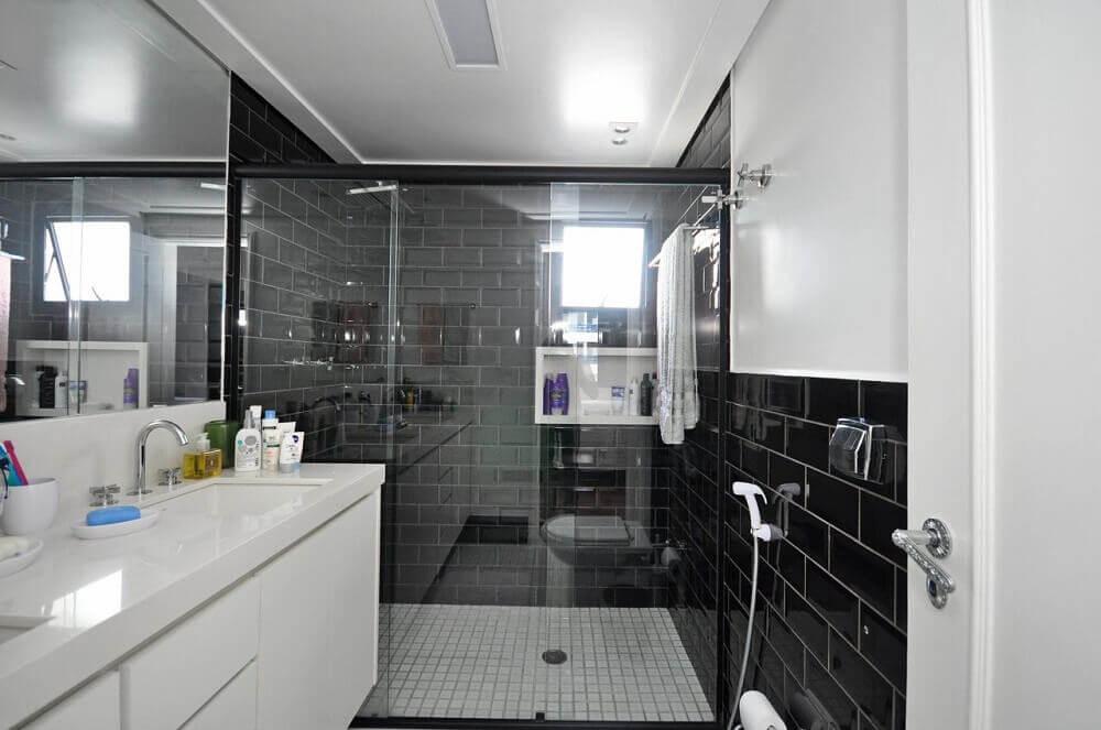 Banheiro pequeno moderno com azulejo de tijolinho preto.
