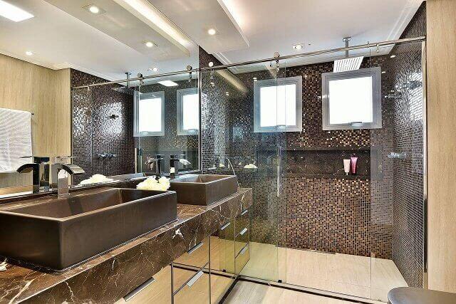 Banheiro pequeno com duas cubas e armário espelhado.