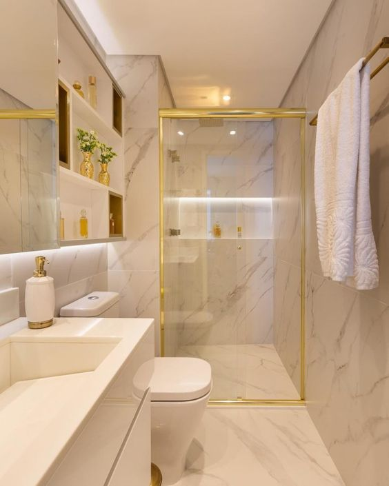 Banheiro pequeno luxuoso com revestimento de mármore e decoração dourada.