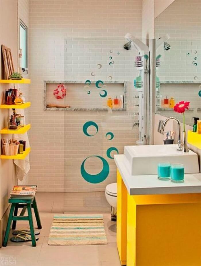 Banheiro pequeno com armário amarelo e prateleira.