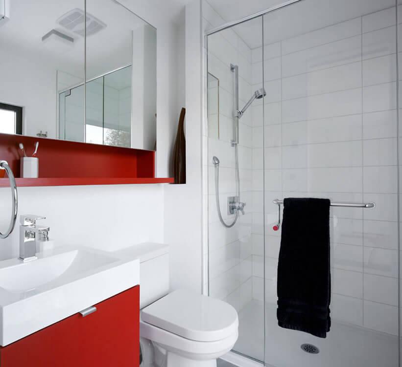 Decoração simples com armário vermelho e azulejo branco.