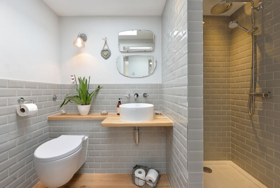Decoração simples com bancada de madeira e azulejo de tijolinho cinza.