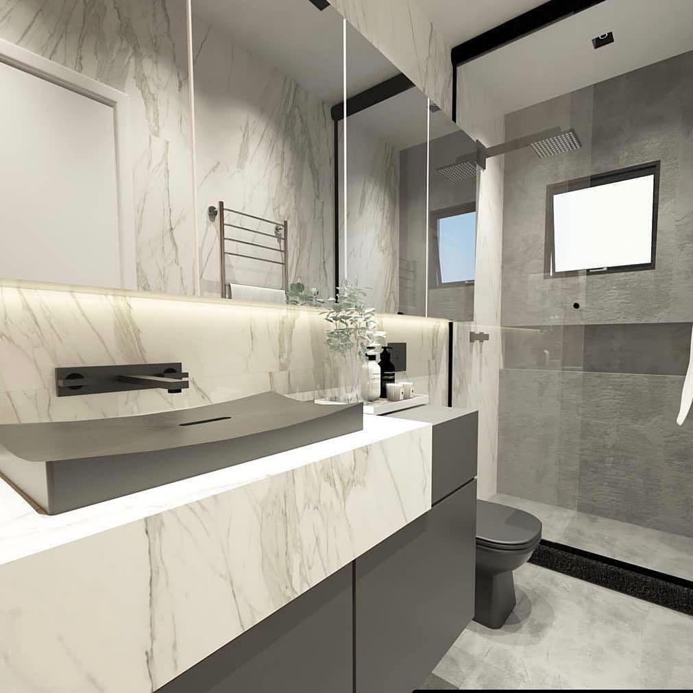 Decoração luxuosa com armário cinza e acabamento de mármore.