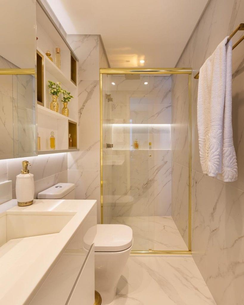 Decoração luxuosa com acabamento de mármore e detalhes dourados.