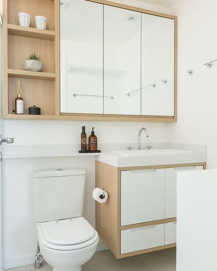 Decoração simples com armário de madeira e e acabamento branco.