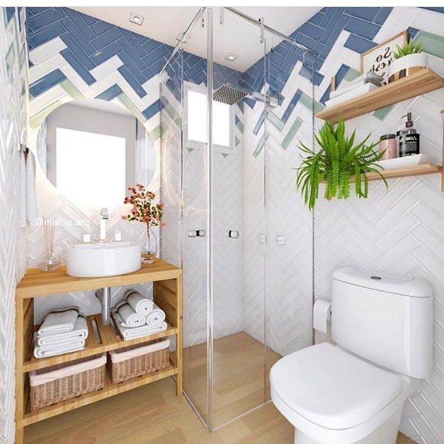 Decoração clean com azulejos de tijolinho colorido, bancada de madeira e vaso de planta.