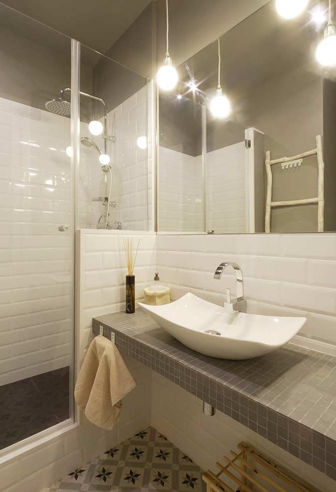 Decoração simples com piso decorado, azulejo de tijolinho branco e cuba moderna.