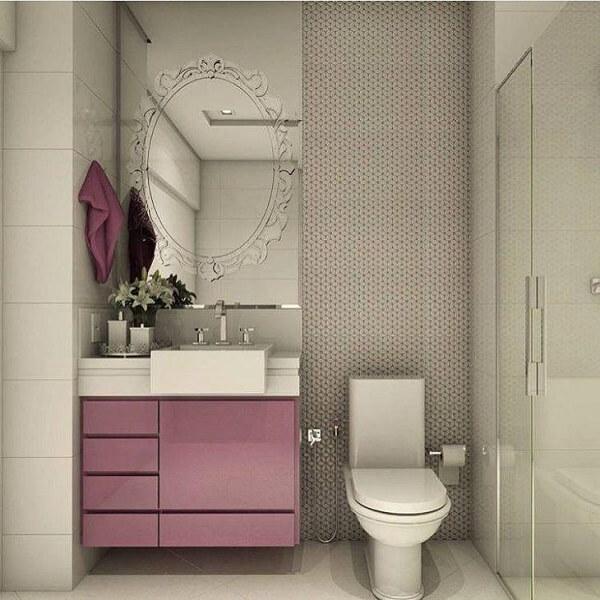 Banheiro pequeno decorado com armário rosa.