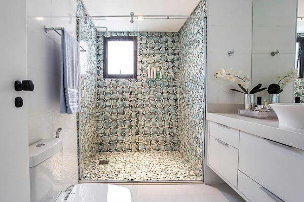 Banheiro pequeno decorado com pastilhas de vidro no box.