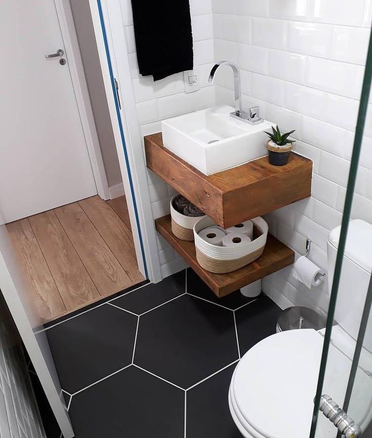 Banheiro pequeno decorado  com piso geométrico preto.