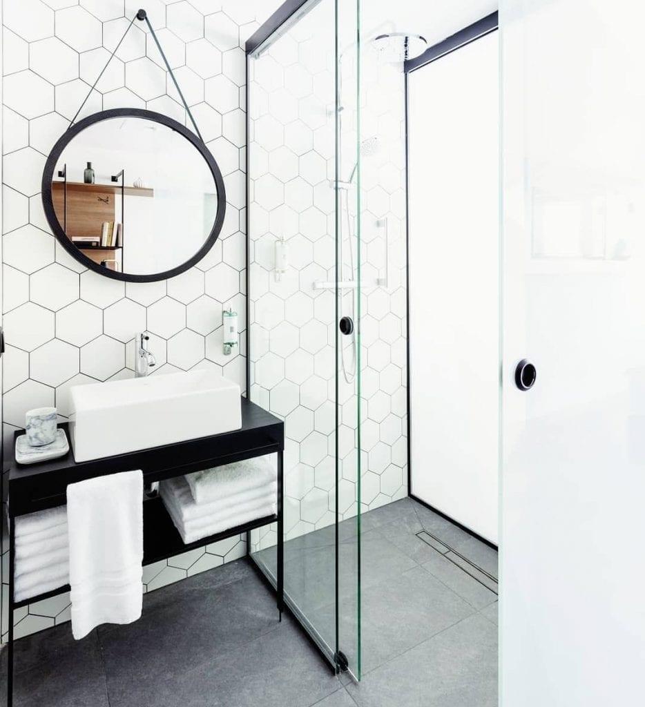Banheiro pequeno decorado com azulejo geométrico branco e piso cinza.