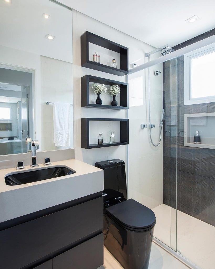 Banheiro pequeno decorado preto e branco.