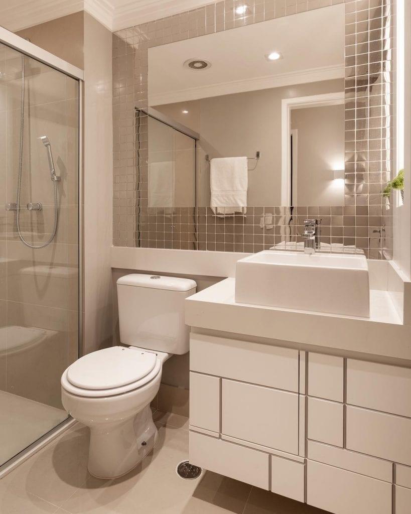 Banheiro pequeno decorado com pastilha metálica.