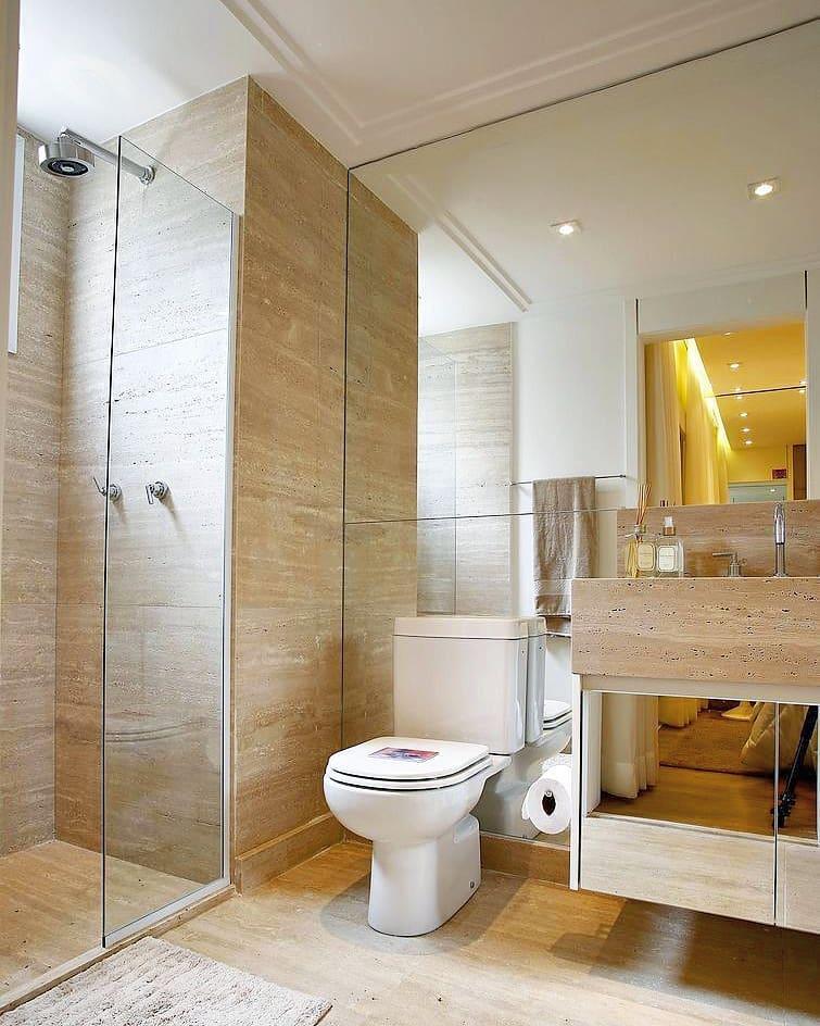 Banheiro pequeno decorado com armário espelhado e acabamento de pedra.