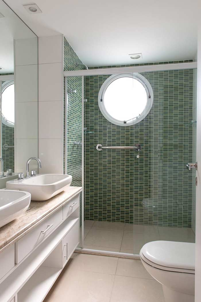 Banheiro pequeno decorado com bancada dupla e pastilhas verdes.