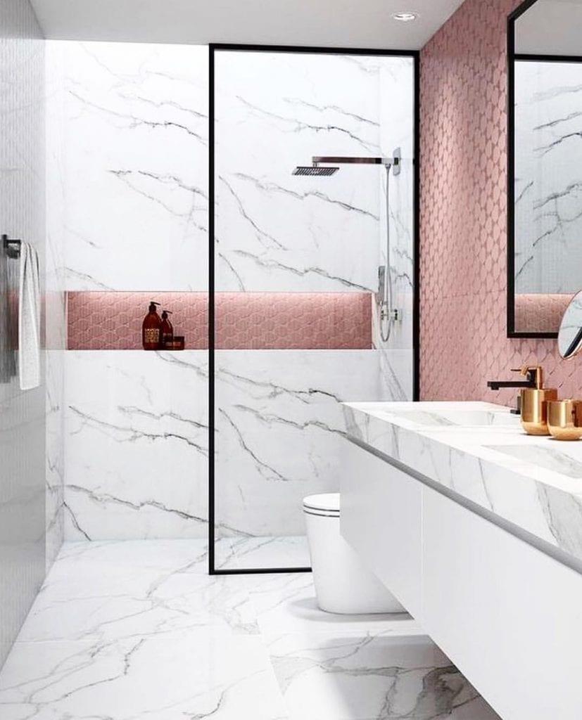 Banheiro pequeno decorado luxuoso com azulejo rosa e acabamento de mármore.