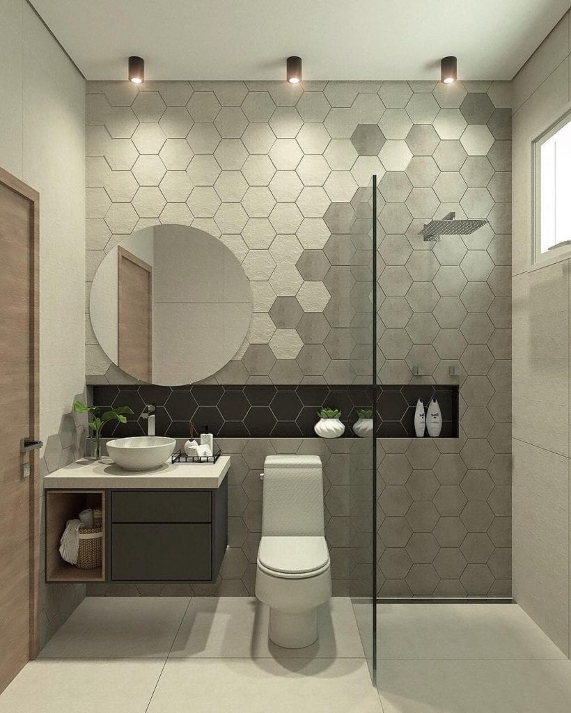 Banheiro pequeno decorado cinza com azulejos geométricos.