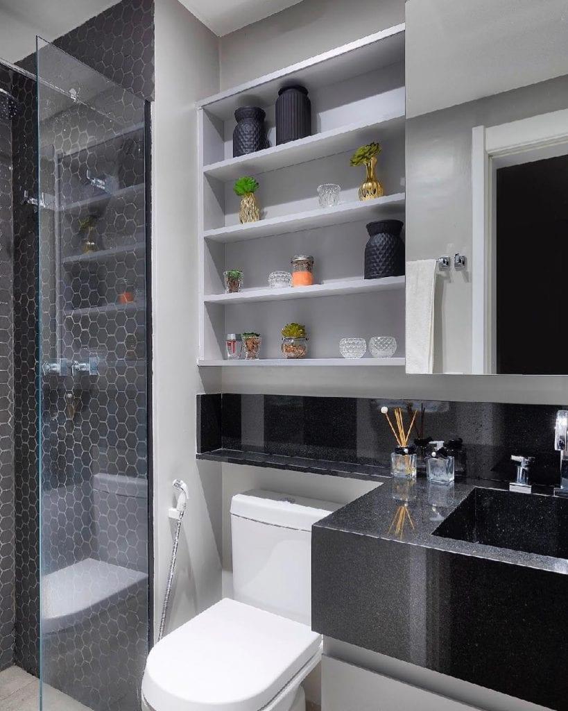 Banheiro pequeno decorado simples com azulejo preto e prateleiras.