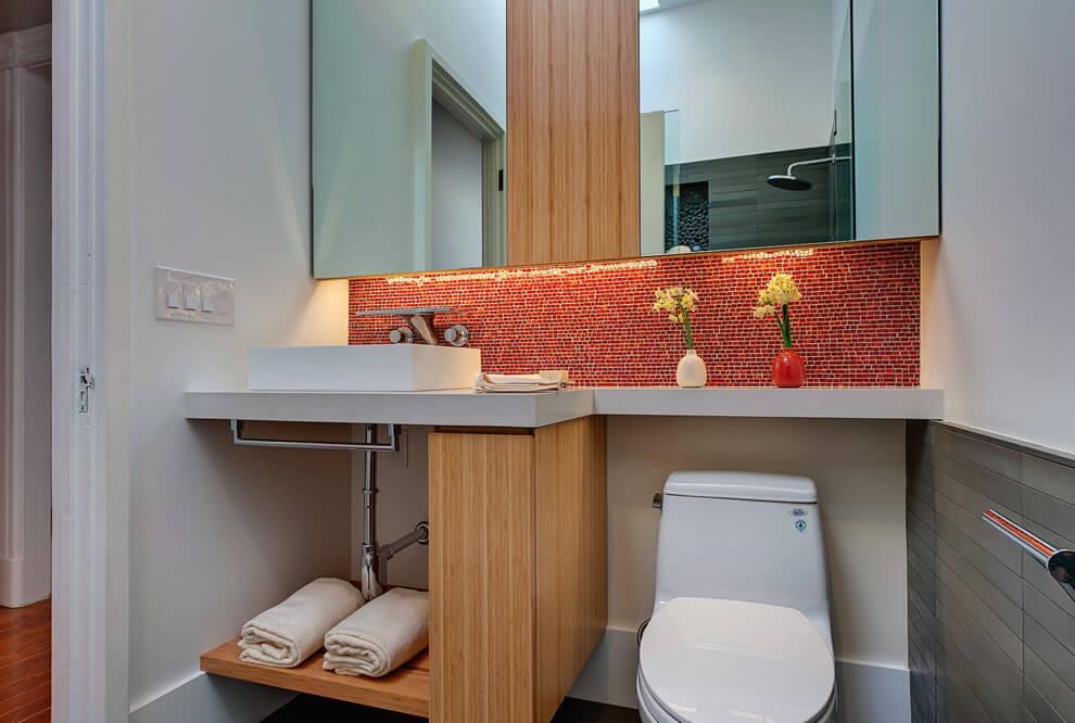 Banheiro pequeno decorado simples com pastilha de vidro vermelho.