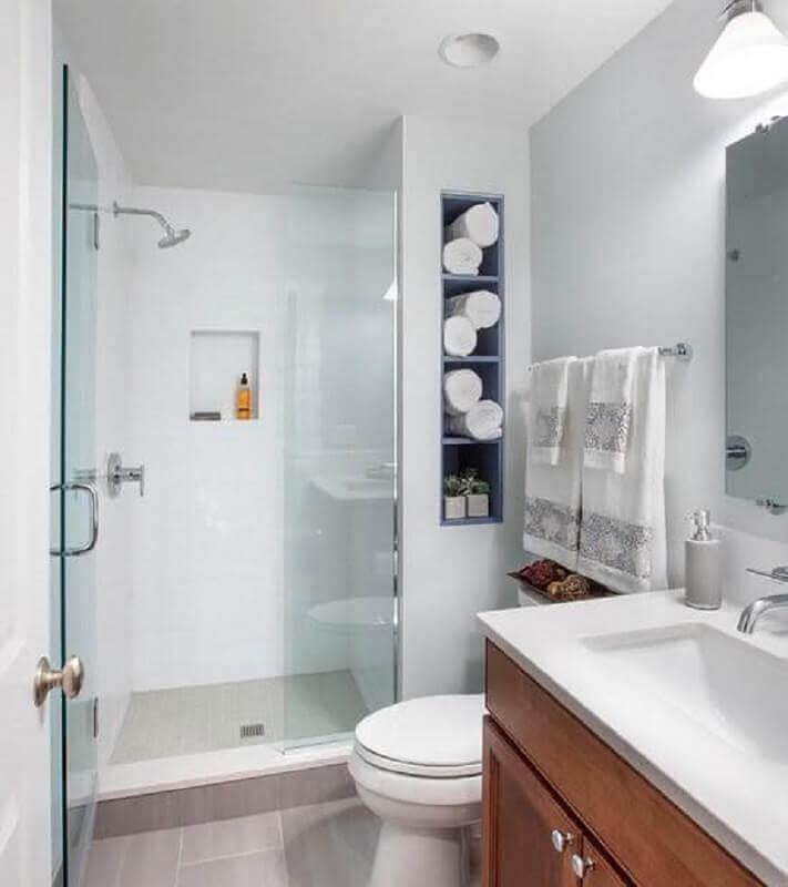 Banheiro simples branco com nicho e armário de madeira.