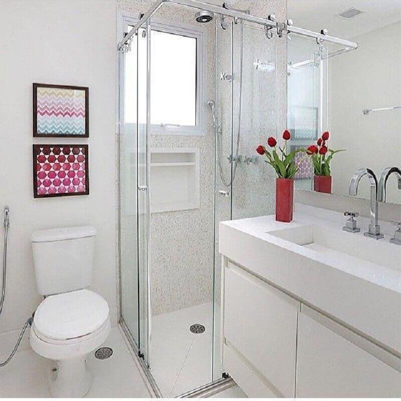 Banheiro simples branco com quadro.