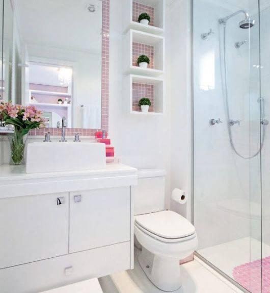 Banheiro simples branco com pastilha rosa.