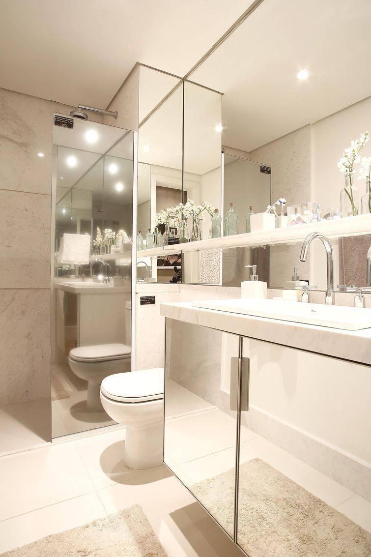 Banheiro simples branco com armário espelhado.