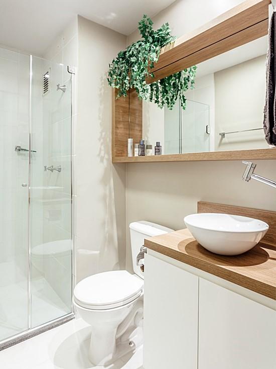 Banheiro simples branco com bancada de madeira.