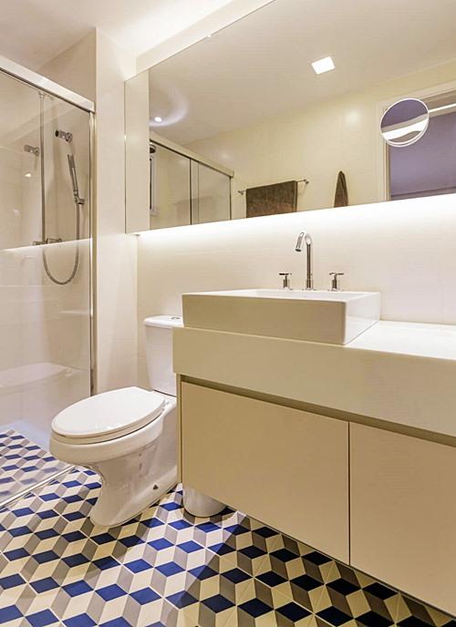 Banheiro simples branco com piso colorido.