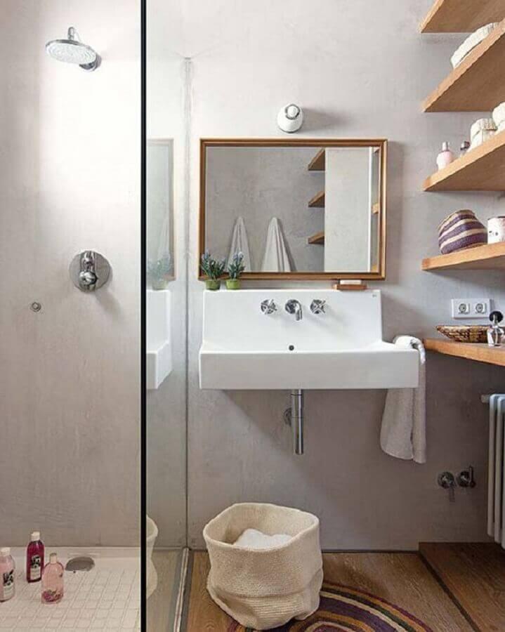 Banheiro simples com lavatório e prateleira de madeira.