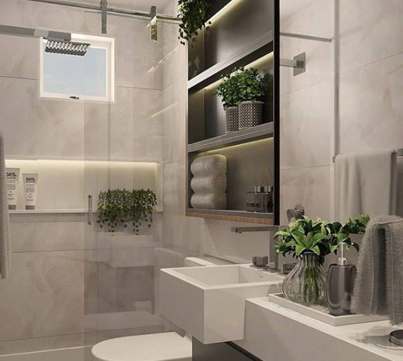 Banheiro simples cinza, prateleira preta e vaso de planta.