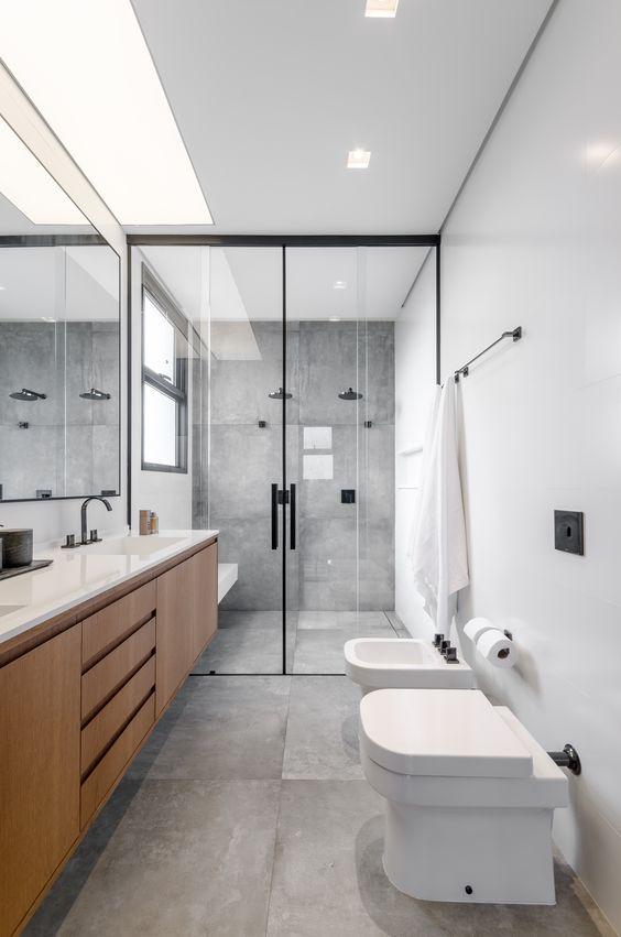 Banheiro simples cinza com armário de madeira.