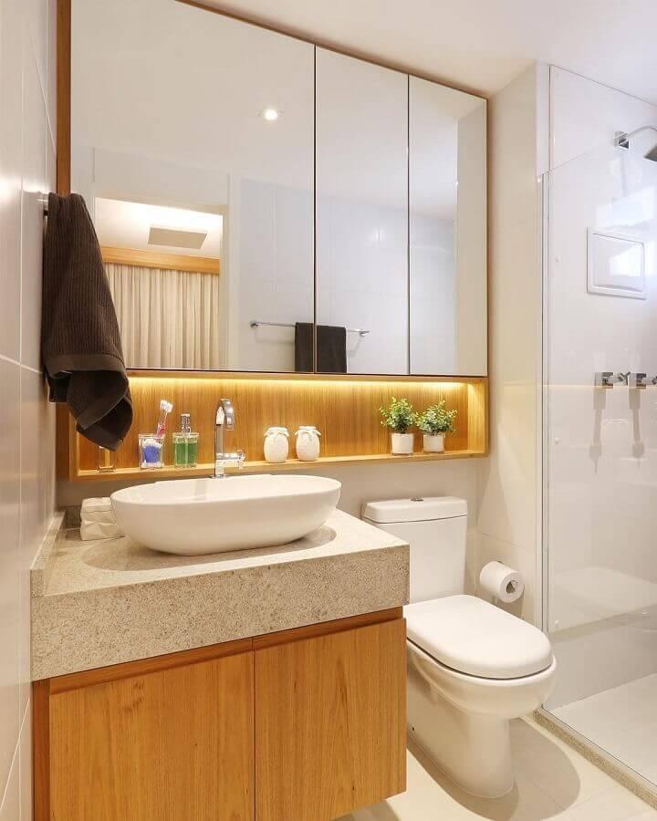 Banheiro simples com armário de madeira e nicho iluminado.