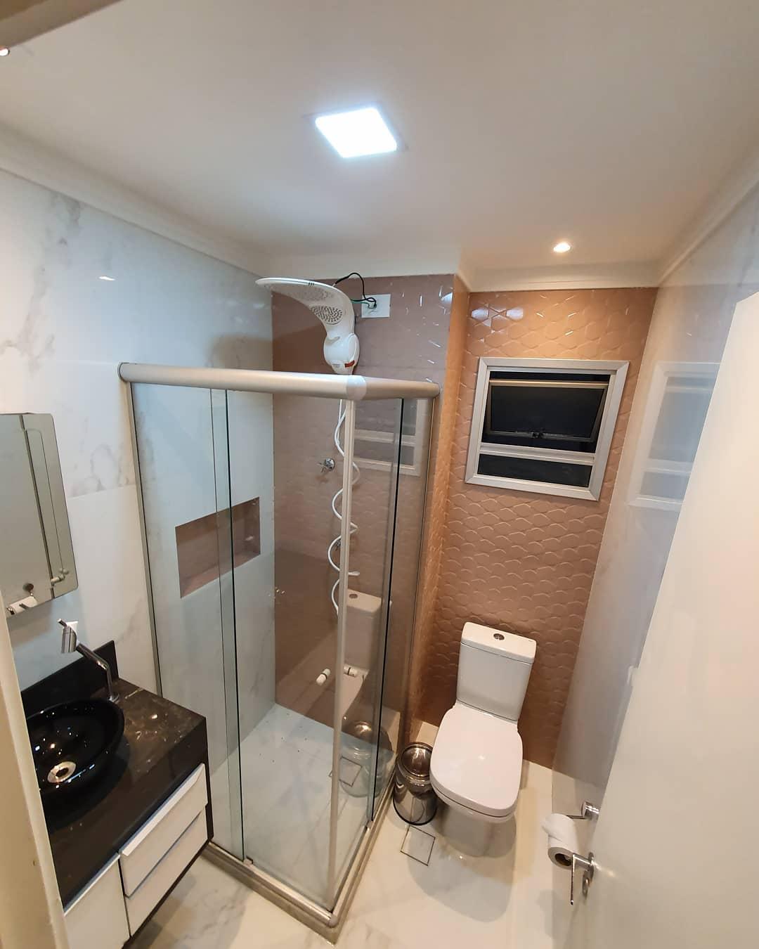 Banheiro simples com azulejo tridimensional marrom.