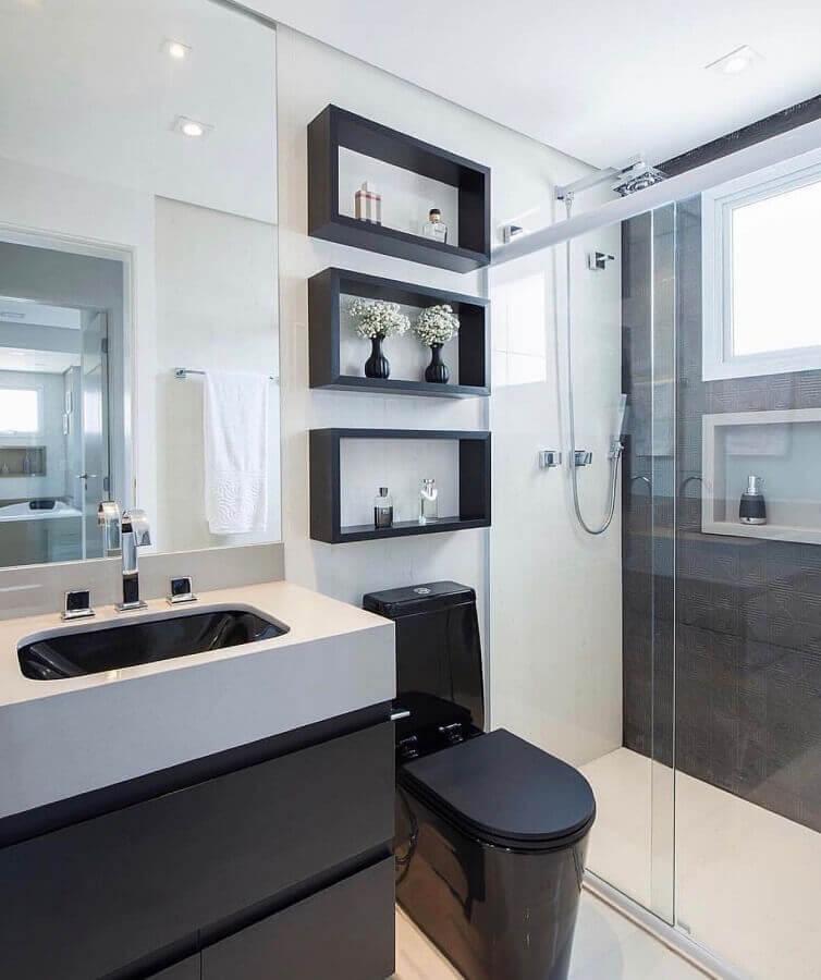 Banheiro simples preto e branco com nicho e vaso sanitário preto.