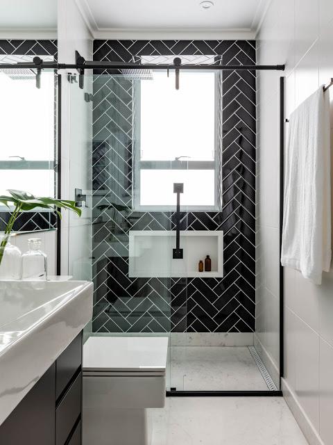 Banheiro simples preto e branco com azulejo de tijolinho preto.