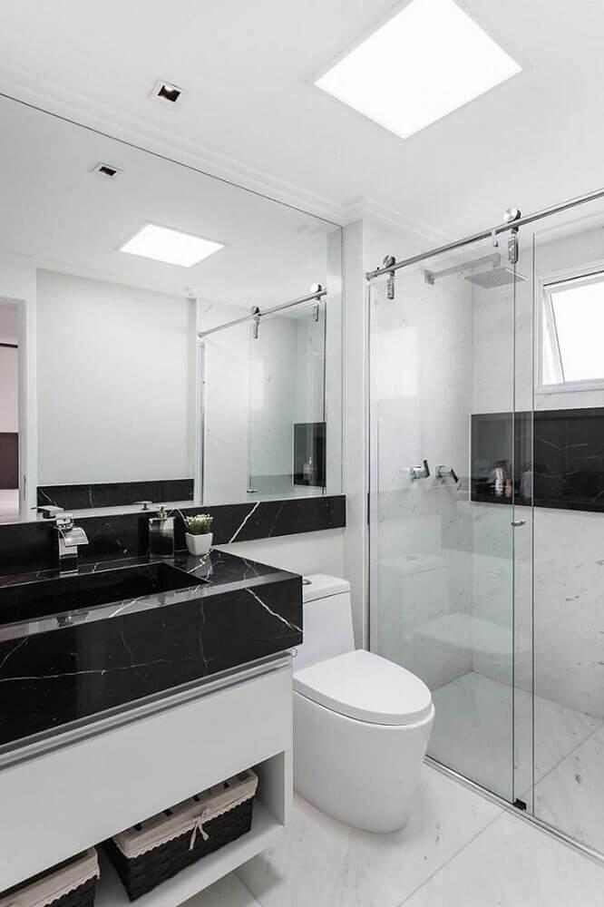 Banheiro simples preto e branco com bancada de porcelanato mesclado.