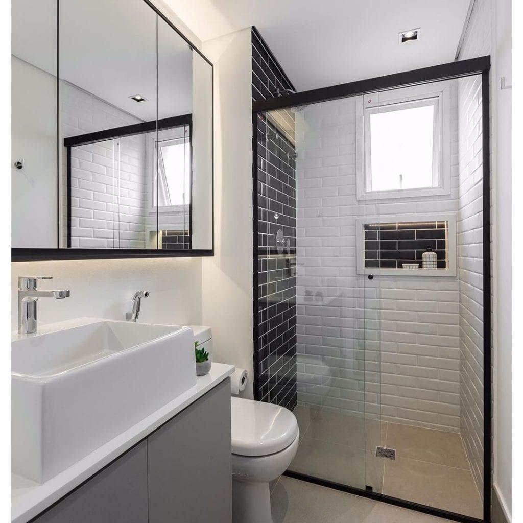 Banheiro simples preto e branco com azulejo preto e branco.