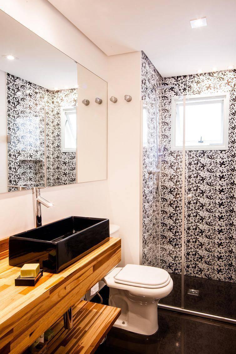 Banheiro simples preto e branco com bancada de madeira.