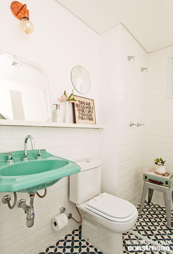Banheiro simples colorido com lavatório verde e ladrilho hidráulico.