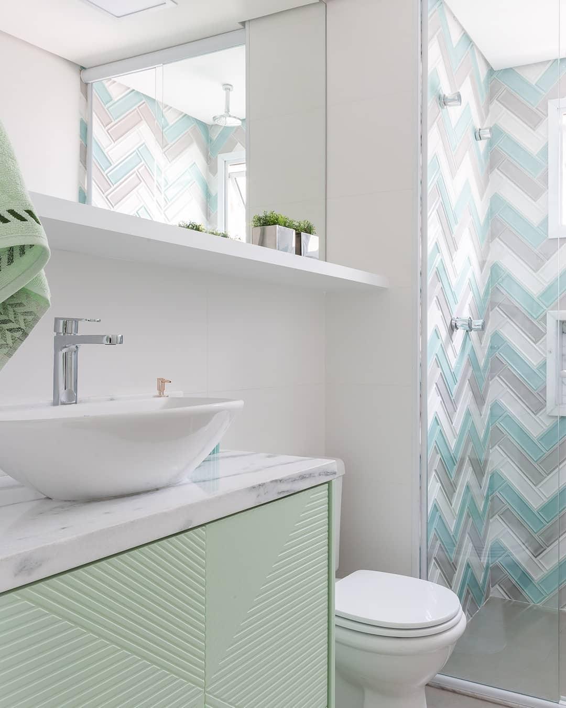 Banheiro simples colorido com armário menta e azulejo de tijolinho.