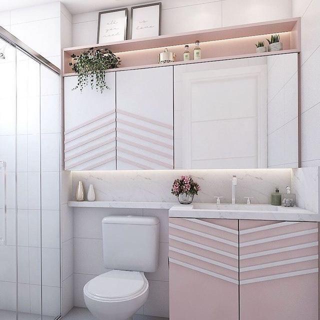 Decoração com armário rosa, espelho com armário e nicho iluminado.