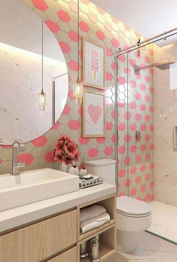 Decoração feminino com azulejo geométrico rosa e armário de madeira.
