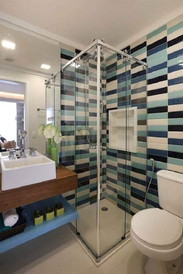 Banheiro simples com azulejo colorido e bancada de madeira.