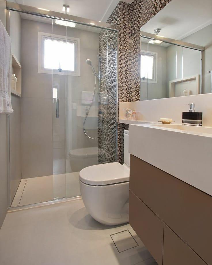 Banheiro simples com armário marrom e pastilhas de vidro.