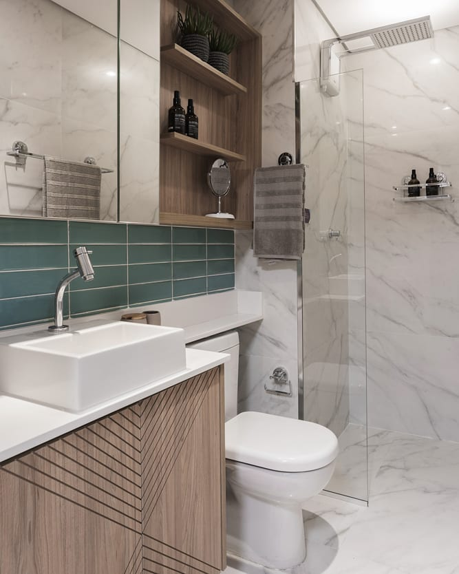 Banheiro simples com armário de madeira e azulejo verde.