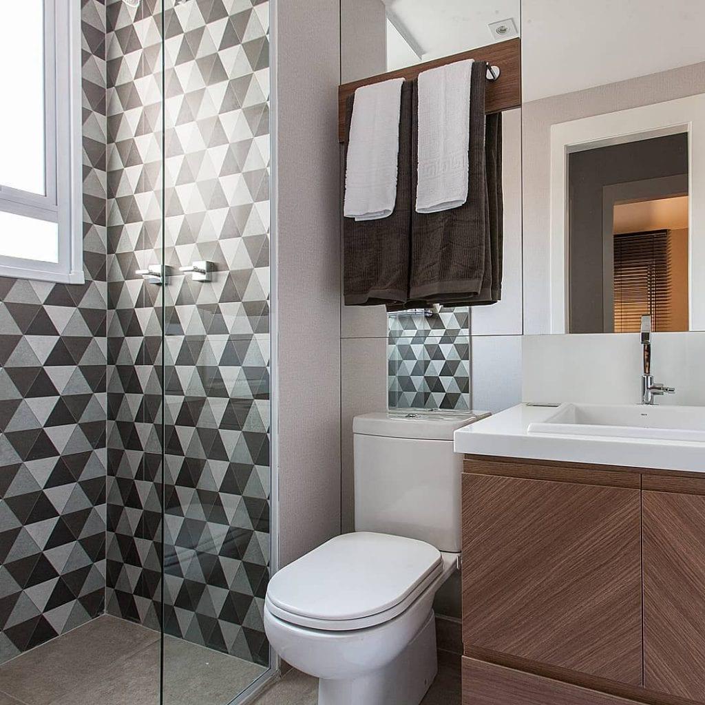 Banheiro simples com armário de madeira e azulejo geométrico.