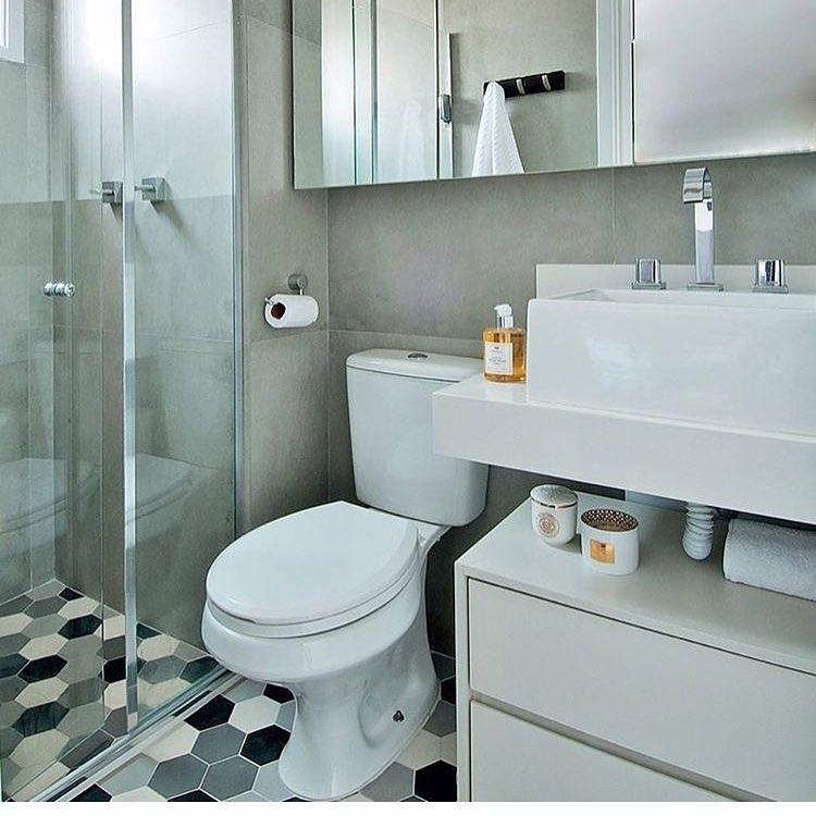Banheiro simples com azulejo cinza e piso decorado geométrico.