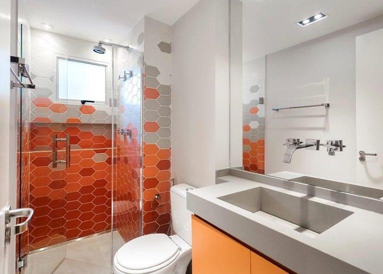 Banheiro simples com armário laranja e azulejo geométrico laranja.