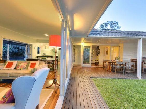 casa em L com varanda de madeira e sala aberta